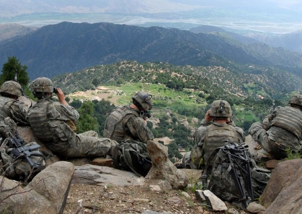 Five U.S. soldiers sit on a ridge looking out at a valley in Afghanistan.