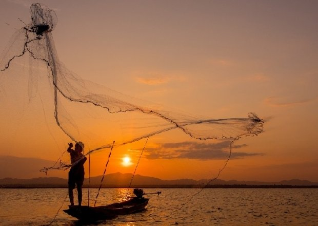 Silhouette Fisherman Throwing Net On Lake Stock Photo