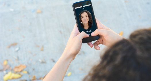 Woman unlocking smartphone with facial recognition technology. Biometric verification and face recognition concept.