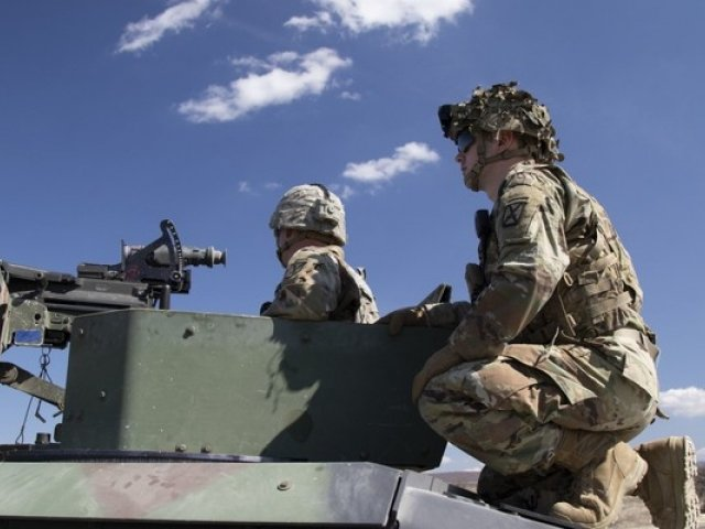 NATO soldiers sit atop a tank