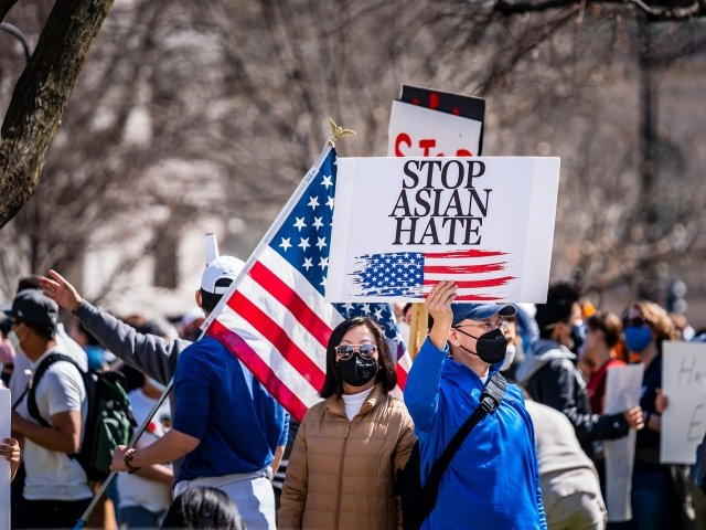 A man stands in a group of protestors wearing a masks, holding a sign with an American flag on it that says Stop Asian Hate.