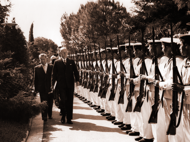 George F. Kennan stands before a line of soldiers