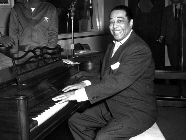 Duke Ellington, a famous jazz musician, poses with his piano at the KFG Radio Studio.