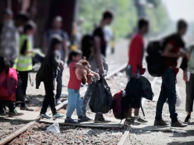 Refugees crossing train tracks in Europe