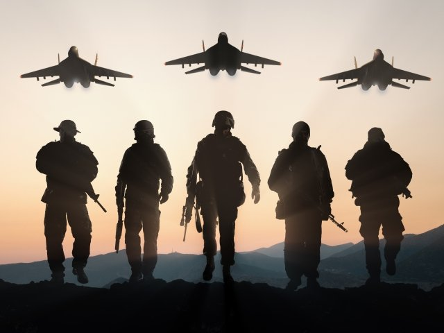 Soldiers walking away from camera with planes overhead