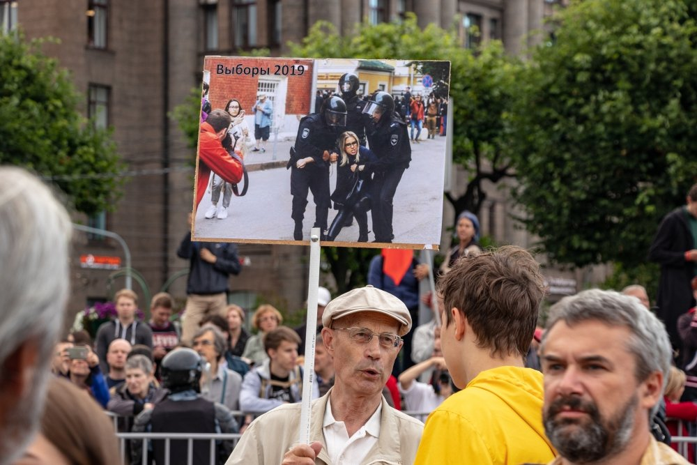 An elderly man holds a banner at a rally with a photo of opposition politician Lyubov Sobol being detained. Source: Shutterstock.
