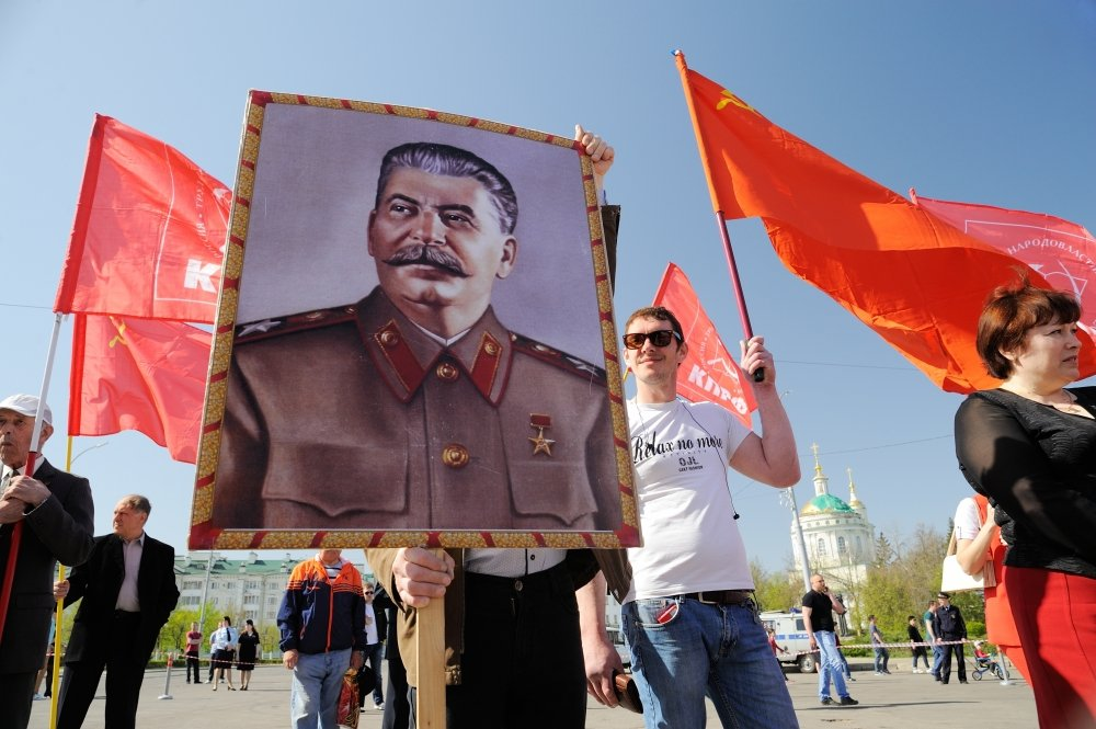 Orel, Russia - May 1, 2017: May demonstration. Young men with Stalin portrait and red Communist flags. Source: Alexey Borodin/Shutterstock