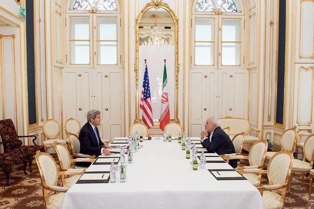 John Kerry at table with Iranian diplomat