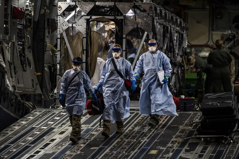 Three U.S. Air Force medical Airmen exit a C-17 Globemaster III following the first-ever operational use of the Transport Isolation System at Ramstein Air Base, Germany, April 10, 2020. The TIS is an infectious disease containment unit designed to minimize contamination risk to aircrew and medical attendants, while allowing in-flight medical care for patients afflicted by a disease—in this case, COVID-19.