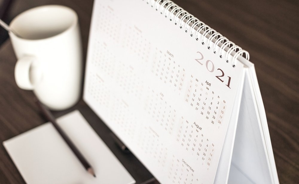A coffee mug sits next to a desk calendar that shows the year 2021