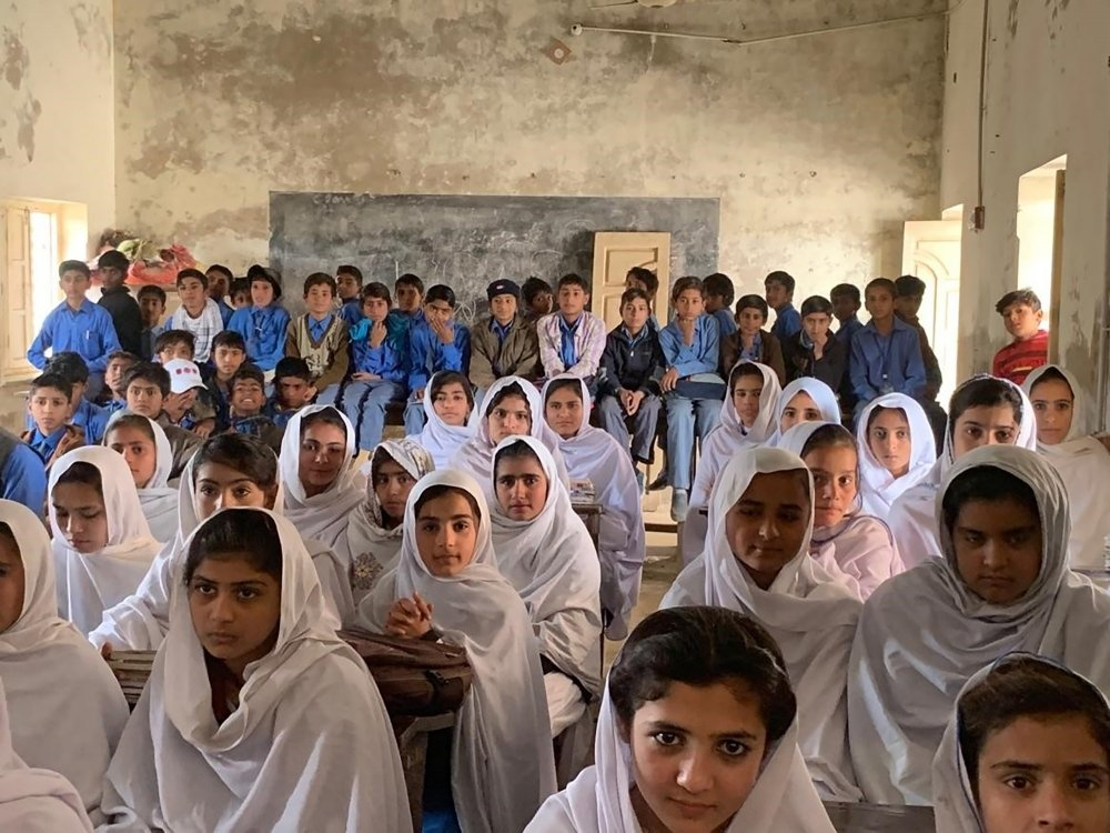 Pakistani children packed into an overcrowded schoolroom.