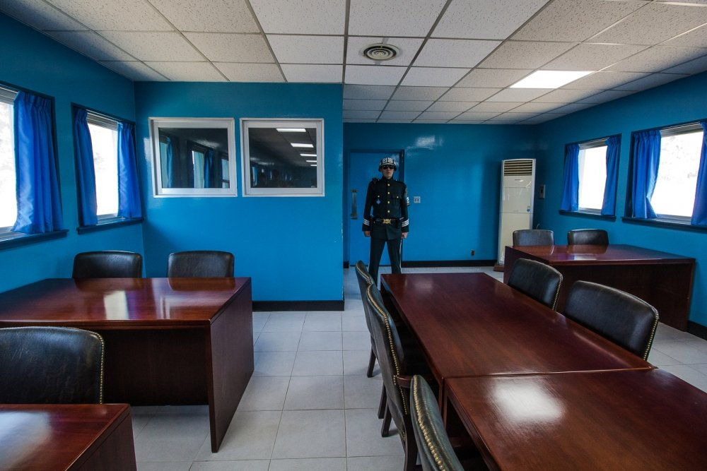 A man stands inside a blue room at the DMZ.