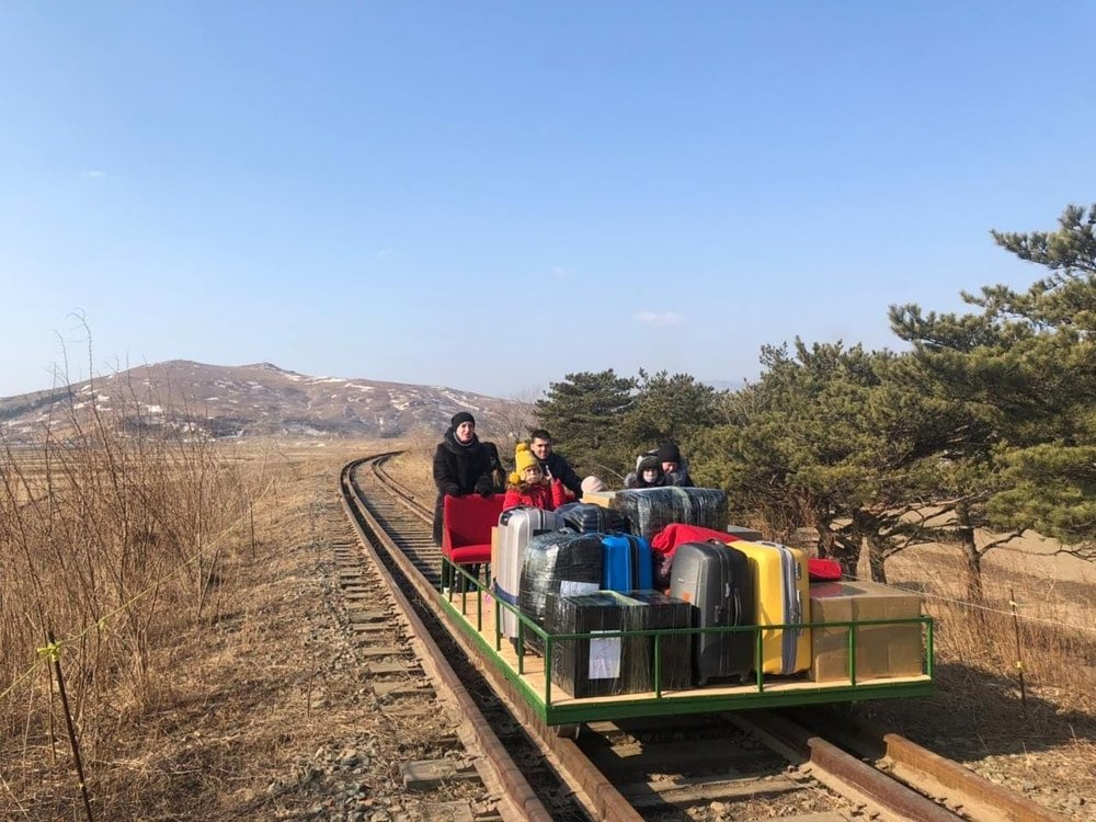 A group of people hand pushing a small railway cart loaded with lugagge.