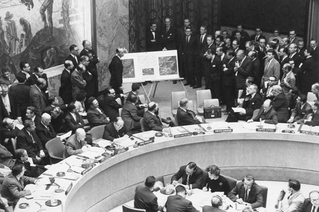 Adlai Stevenson shows missiles to UN Security Council with David Parker standing, October 1962