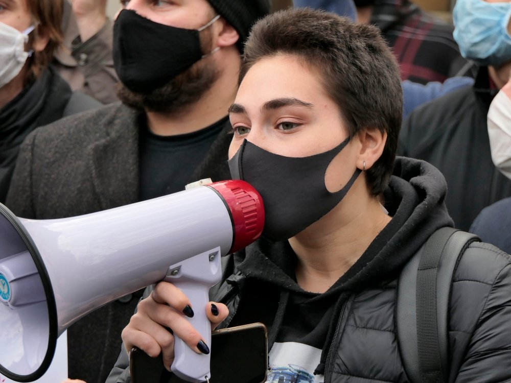 Kiev/Ukraine - October 26, 2020: young dark haired woman with medical mask on face shout out slogans to loudspeaker at street protest rally against abortion ban in Poland near Polish embassy in Kyiv