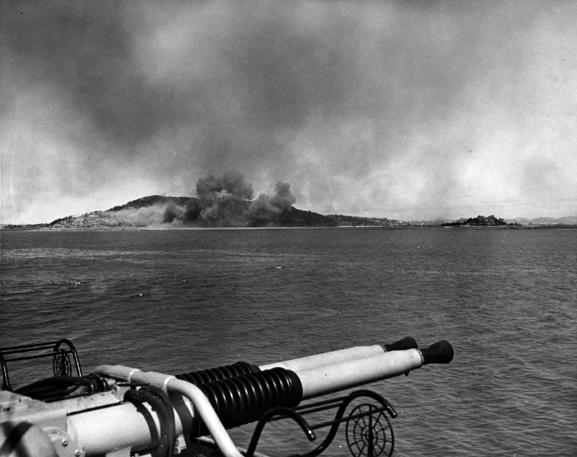 A black and white image of an island with smoke rising in the distance.