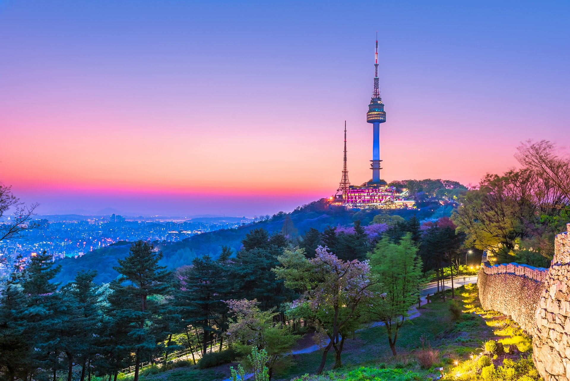 Two communication towers on the top of a hill at sunset