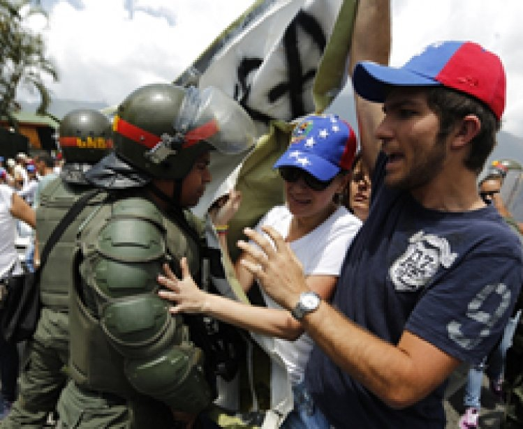Anti-government protesters scuffle with national guards as they march by Generalisimo Francisco de Miranda Airbase in Caracas March 4, 2014.