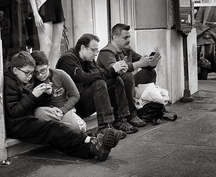 People holding smart phones while sitting. Source: Wikimedia Commons.