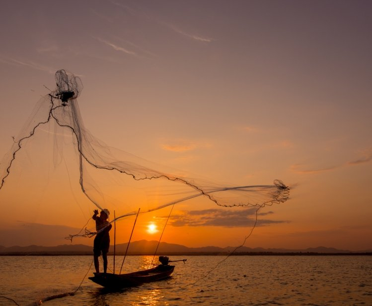 Silhouette of fisherman throwing net on the lake, Shutterstock