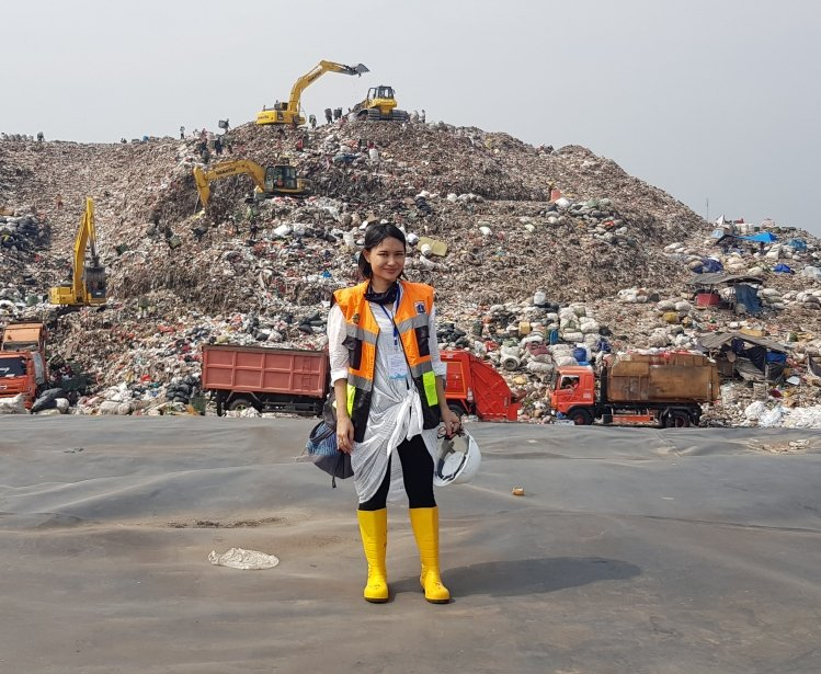 Woman standing in front of multi-colored landfill site