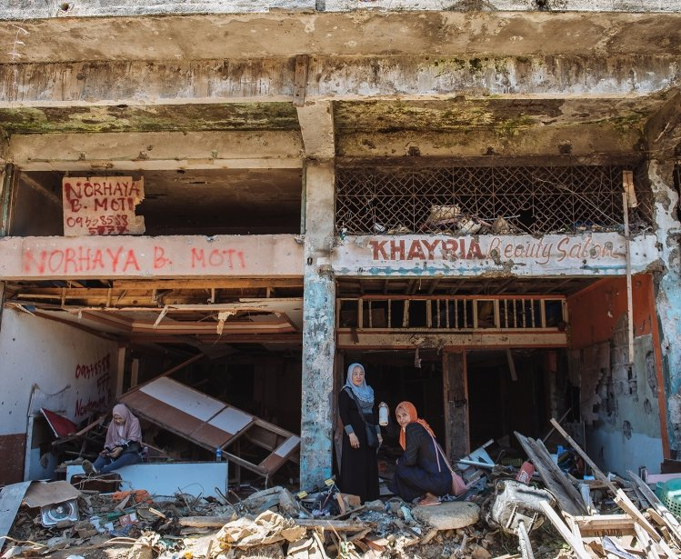 Two women in the ruins of a building in Marawi City, Philippines.
