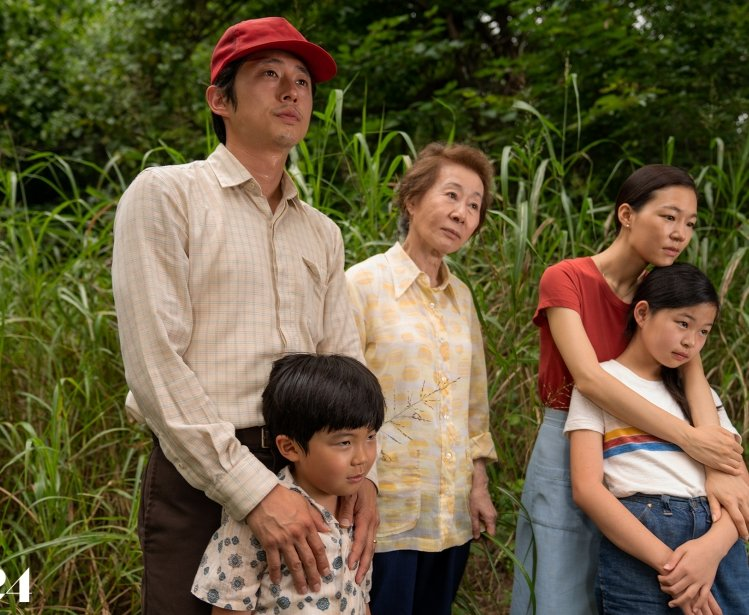A family of five people stand in a wooded area.