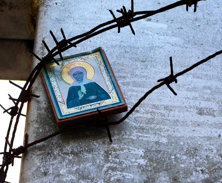 The icon of the Holy Mother is fixed under the barbed wire on the memorial cross to the victims of the Gulag. Stalinist repression.