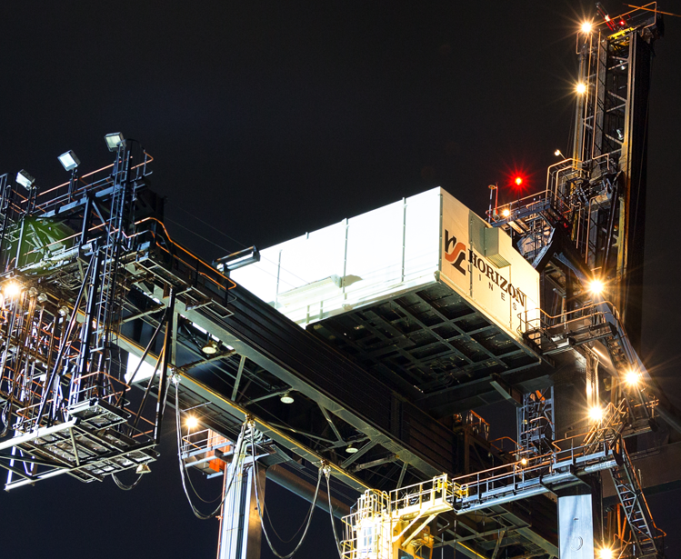 Dutch Harbor, Unalaska, Alaska, USA - August 14th, 2017: Night view of a port crane for shipping containers operated by Horizon Lines located at the port of Unalaska, Alaska