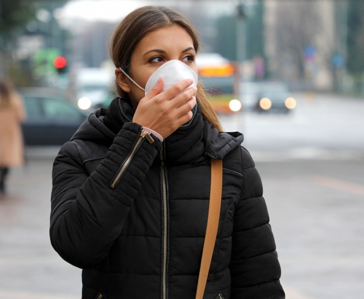 COVID-19 Pandemic Coronavirus Woman in city street wearing protective face mask