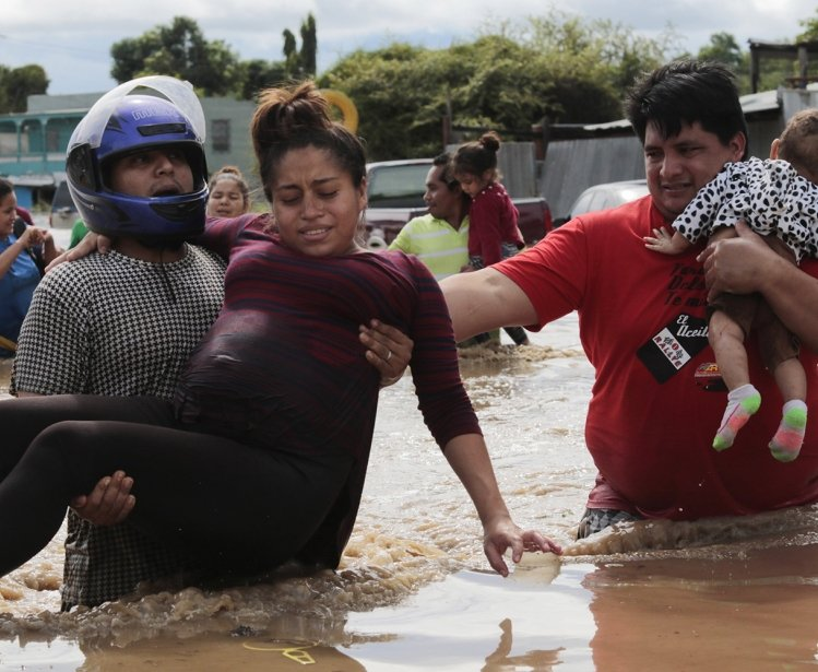 A pregnant woman is carried out of an area flooded by water brought by Hurricane Eta in Planeta, Honduras, Nov. 5, 2020.