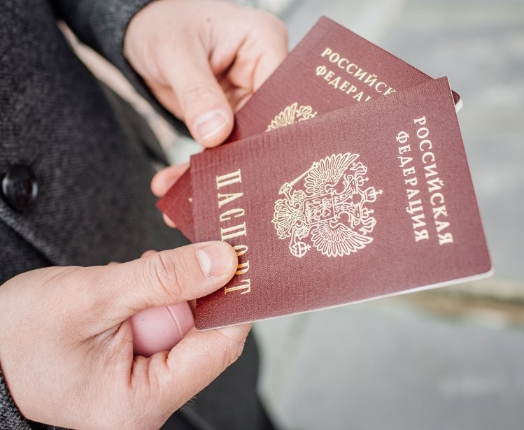 Two russian passports in hand. Russian official document on outdoor background