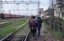 Migrants walking along train tracks in Serbia. Source: Shutterstock.
