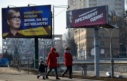 People walking near political billboards of Ukrainian candidates of presidential election, Kyiv.