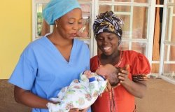 Two women, one in blue scrubs holding a baby