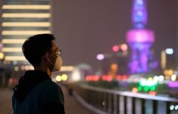A young man wearing surgical mask looking at Oriental Pearl TV Tower in Shanghai at night