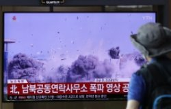 A man watching a TV screen showing a news program with a video of the demolition of the inter-Korean liaison office building in Kaesong, North Korea.