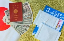 Cloth masks, a leaflet, and 100,000 yen cash sitting on a background with a Japanese flag.