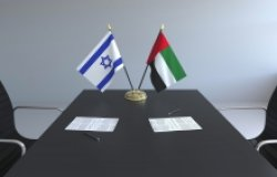 The flags of Israel and the UAE on a conference room table.