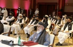 The Taliban negotiator sits at a table with his delegation behind him at the peace talks in Doha, Qatar.