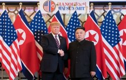 Donald J. Trump stands next to Kim Jong Un as they shake hands and pose in front of U.S. and North Korean flags