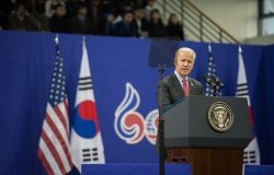 Joe Biden stands at a podium delivering a speech in front of U.S. and South Korean flags