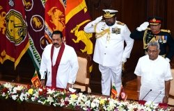 Prime Minister Mahinda Rajapaksa and President Gotabaya Rajapaksa stand in front of two soldiers at a swearing in ceremony