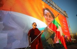 A man in red robes stands with a flag in front of a banner of Aung San Suu Kyi