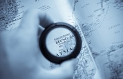 A hand holds a magnifying glass that is circling Brunei on a map.