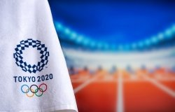 A towel with the logo for the Tokyo 2020 olympics in the foreground with track and field starting blocks in the background in soft focus