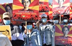 A crowd of protestors wearing surgical masks carry signs reading Please Save our Leader - Future - Hope with a photo of Aung San Suu Kyi