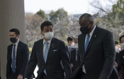 A group of men wearing medical masks talk as they they are walking into a building.