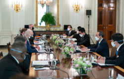 A group of men including President Biden and PM Suga sit around a conference table