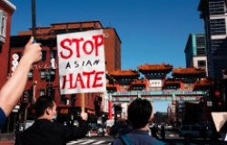 People march in the streets of Chinatown, one holding a sign that reads Stop Asian Hate